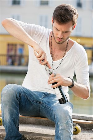 Man opening a wine bottle with a corkscrew, Paris, Ile-de-France, France Stock Photo - Premium Royalty-Free, Code: 6108-05873087