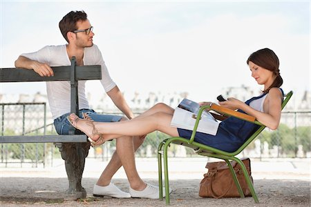 Woman using a mobile phone with a man sitting in front of her, Jardin des Tuileries, Paris, Ile-de-France, France Stock Photo - Premium Royalty-Free, Code: 6108-05873097