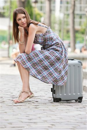 Woman sitting on the suitcase at the roadside, Paris, Ile-de-France, France Stock Photo - Premium Royalty-Free, Code: 6108-05873247