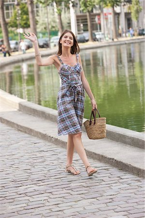 Woman waving her hand and smiling, Paris, Ile-de-France, France Stock Photo - Premium Royalty-Free, Code: 6108-05873289