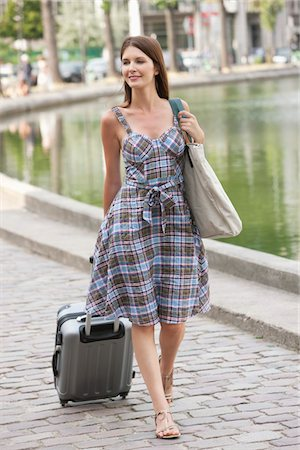 Woman pulling a suitcase and smiling, Paris, Ile-de-France, France Stock Photo - Premium Royalty-Free, Code: 6108-05873205