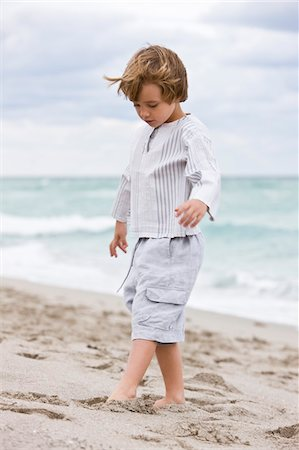 Boy playing on the beach Stock Photo - Premium Royalty-Free, Code: 6108-05873842