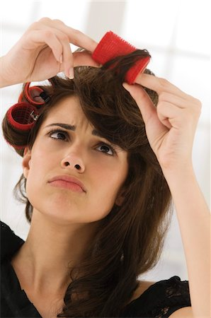 Close-up of a woman removing hair curlers Stock Photo - Premium Royalty-Free, Code: 6108-05873815