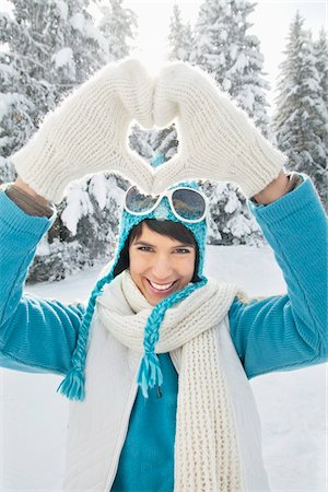 Young woman in winter clothes making heart shape with hands Stock Photo - Premium Royalty-Free, Code: 6108-05874559