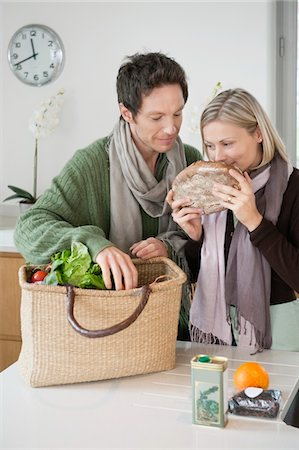 smelly - Woman smelling a loaf of bread with her husband standing beside her Stock Photo - Premium Royalty-Free, Code: 6108-05874623