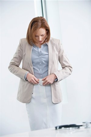 Woman getting dressed in an office Stock Photo - Premium Royalty-Free, Code: 6108-05874766