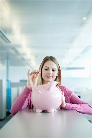 Businesswoman inserting a coin into a piggy bank Stock Photo - Premium Royalty-Free, Code: 6108-05874788