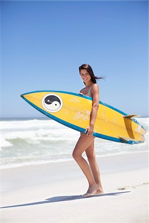Woman walking on the beach with surfboard Stock Photo - Premium Royalty-Free, Code: 6108-05874896
