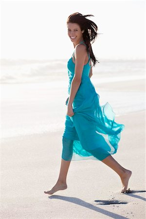 Portrait of a young woman walking on beach Stock Photo - Premium Royalty-Free, Code: 6108-05874945