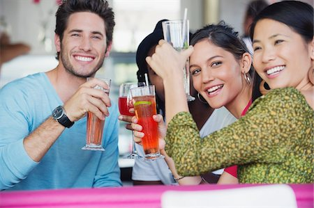 Portrait of friends toasting drinks in a restaurant Stock Photo - Premium Royalty-Free, Code: 6108-05874955
