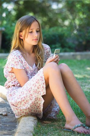 preteen beauty - Cute little girl using a mobile phone outdoors Stock Photo - Premium Royalty-Free, Code: 6108-05874968