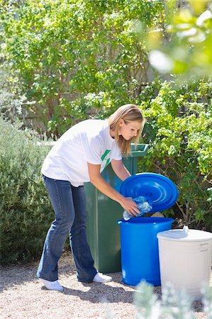 Woman throwing water bottles in garbage bin Stock Photo - Premium Royalty-Free, Code: 6108-05874923