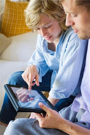 preteen touch - Man and a little boy looking at digital tablet Stock Photo - Premium Royalty-Free, Code: 6108-05874938
