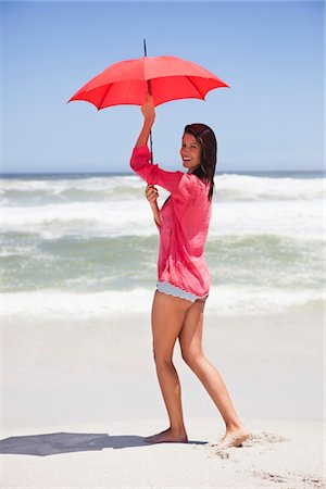 Woman walking on the beach with an umbrella Stock Photo - Premium Royalty-Free, Code: 6108-05875090