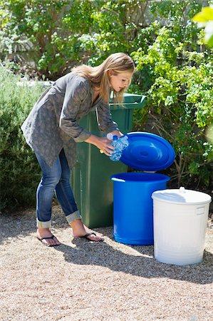 Woman throwing water bottles in garbage bin Stock Photo - Premium Royalty-Free, Code: 6108-05875009