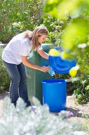 Woman throwing water bottle in garbage bin Stock Photo - Premium Royalty-Free, Code: 6108-05875014