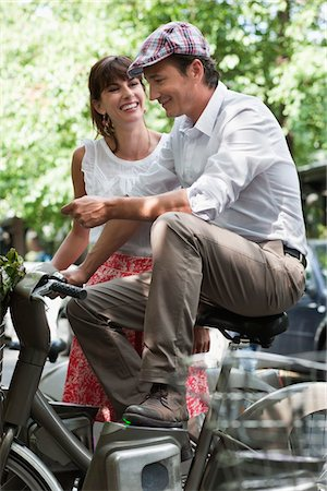 Couple riding bicycles and smiling, Paris, Ile-de-France, France Stock Photo - Premium Royalty-Free, Code: 6108-05875141