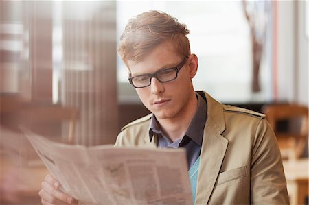 Man reading a newspaper in a restaurant Stock Photo - Premium Royalty-Free, Code: 6108-06165954