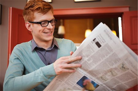 Man reading a newspaper in a restaurant Stock Photo - Premium Royalty-Free, Code: 6108-06165965