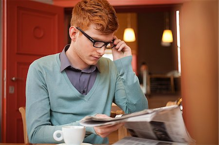 Man reading a newspaper in a restaurant Stock Photo - Premium Royalty-Free, Code: 6108-06165969