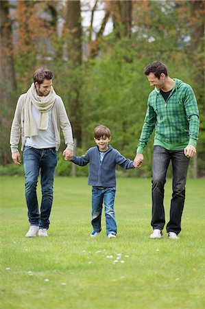 Boy walking with two men in a park Stock Photo - Premium Royalty-Free, Code: 6108-06165978