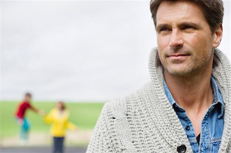 farm and boys - Close-up of a man thinking with his son and wife in the background Stock Photo - Premium Royalty-Free, Code: 6108-06165995