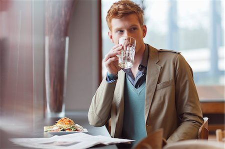 Man sitting in a restaurant and drinking water Stock Photo - Premium Royalty-Free, Code: 6108-06166043