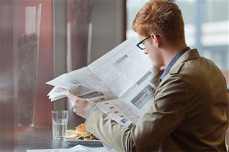 Man sitting in a restaurant and reading a newspaper Stock Photo - Premium Royalty-Free, Code: 6108-06166047
