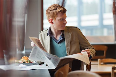 Man sitting in a restaurant and reading a newspaper Stock Photo - Premium Royalty-Free, Code: 6108-06166053