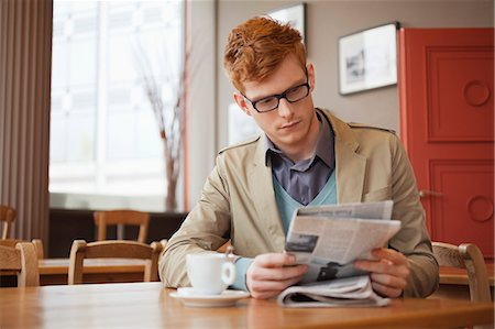 Man sitting in a restaurant and reading a newspaper Stock Photo - Premium Royalty-Free, Code: 6108-06166066