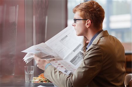 Man sitting in a restaurant and reading a newspaper Stock Photo - Premium Royalty-Free, Code: 6108-06166092