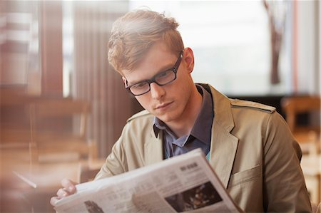 Man sitting in a restaurant and reading a newspaper Stock Photo - Premium Royalty-Free, Code: 6108-06166094