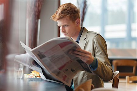Man sitting in a restaurant and reading a newspaper Stock Photo - Premium Royalty-Free, Code: 6108-06166036