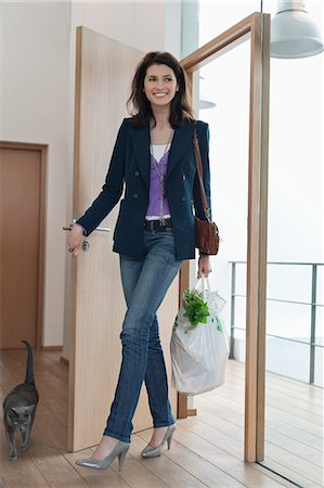 Woman arriving home with a bag of groceries Stock Photo - Premium Royalty-Free, Code: 6108-06166162