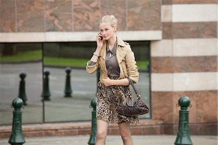 Businesswoman crossing the road while talking on a mobile phone Stock Photo - Premium Royalty-Free, Code: 6108-06166107