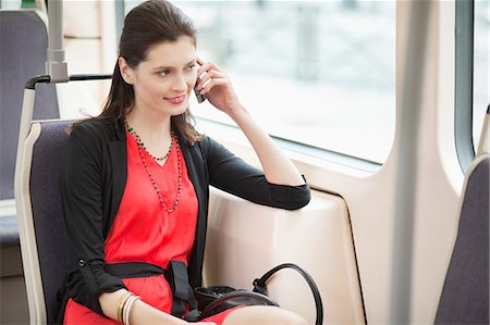 Woman traveling in a tram and talking on a mobile phone Stock Photo - Premium Royalty-Free, Code: 6108-06166105