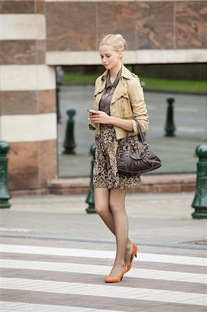 Businesswoman crossing the road while using a mobile phone Stock Photo - Premium Royalty-Free, Code: 6108-06166127