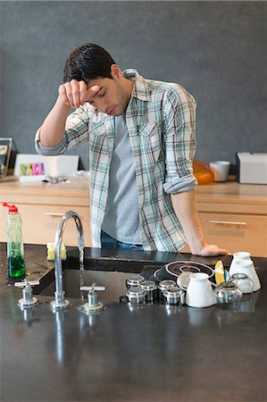 domestic life - Man looking tired after washing dishes Stock Photo - Premium Royalty-Free, Code: 6108-06166260