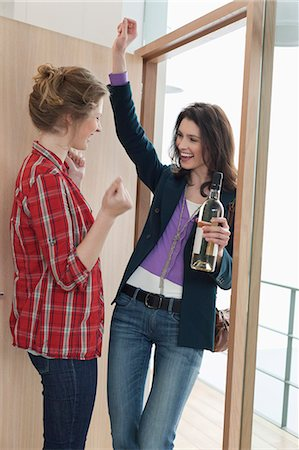 Woman arriving at her friends home with a wine bottle Stock Photo - Premium Royalty-Free, Code: 6108-06166343