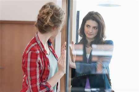 Two female friends looking at each other through a glass door Stock Photo - Premium Royalty-Free, Code: 6108-06166347