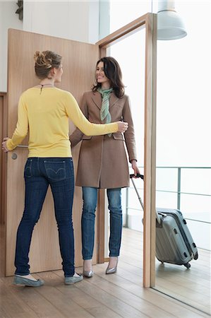 Woman welcoming her friend at doorway Stock Photo - Premium Royalty-Free, Code: 6108-06166352