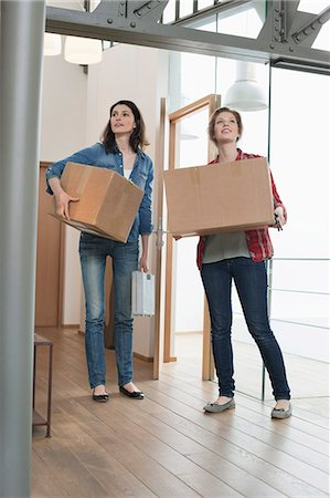 Female friends carrying cardboard boxes at home Stock Photo - Premium Royalty-Free, Code: 6108-06166355