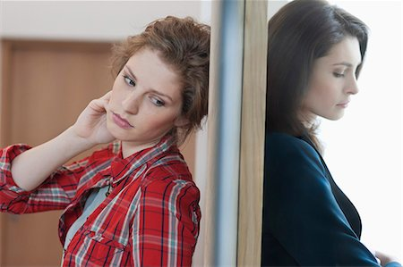 Two female friends standing back to back against a door Stock Photo - Premium Royalty-Free, Code: 6108-06166369