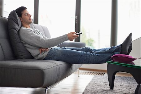 Man reclining on a couch and watching television Stock Photo - Premium Royalty-Free, Code: 6108-06166312