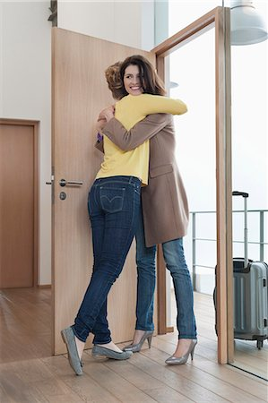 Woman welcoming her friend at doorway Stock Photo - Premium Royalty-Free, Code: 6108-06166329