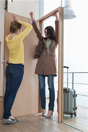 Woman welcoming her friend at doorway Stock Photo - Premium Royalty-Free, Code: 6108-06166339