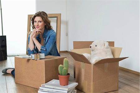 Woman leaning on a cardboard box and smiling Stock Photo - Premium Royalty-Free, Code: 6108-06166461