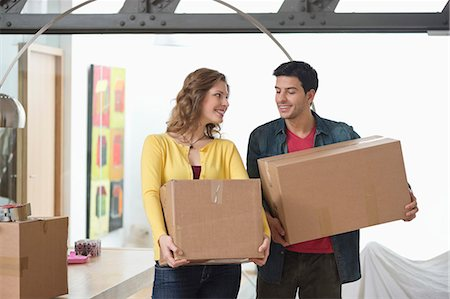 Couple carrying cardboard boxes and smiling Stock Photo - Premium Royalty-Free, Code: 6108-06166469
