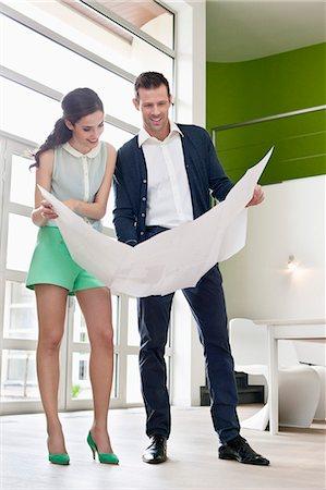 Couple reading a blueprint Stock Photo - Premium Royalty-Free, Code: 6108-06166491