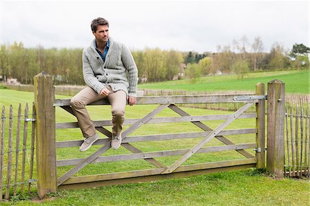 Man sitting on the gate of a cottage Stock Photo - Premium Royalty-Free, Code: 6108-06166542